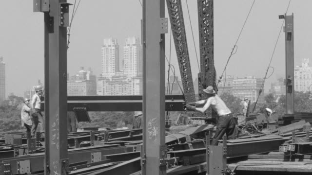 ms pan shot of workers working on 5th floor at steel building under construction - steel stock videos & royalty-free footage