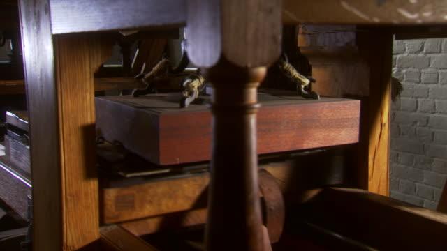 ms pan shot of working colonial era printing press  / williamsburg, virginia, united states - historische szene stock-videos und b-roll-filmmaterial