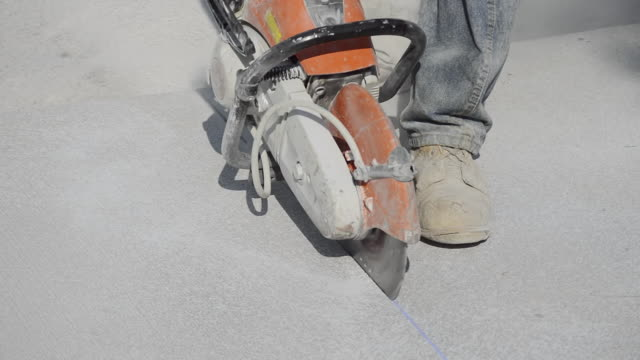 ms shot of workman using concrete saw to cut control joints in one day old concrete / valparaiso, indiana, united states - condition stock videos & royalty-free footage