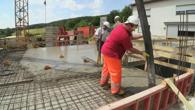 MS Shot of workmen casting concrete at house construction, building site / Hermeskeil, Rhineland Palatinate, Germany