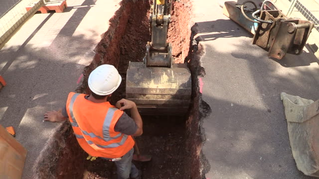 ms shot of workmen engraving on street for works at sewage pipe / saarburg, rhineland palatinate, germany - 掘る点の映像素材/bロール