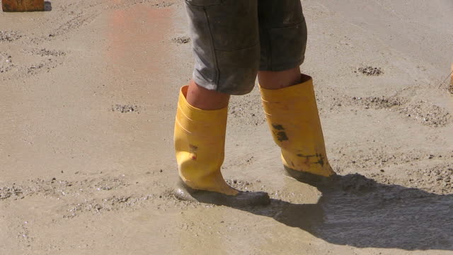 cu shot of workmen leveling and smoothing cement filling area at house construction, building site / hermeskeil, rhineland palatinate, germany - wellington boot stock videos & royalty-free footage