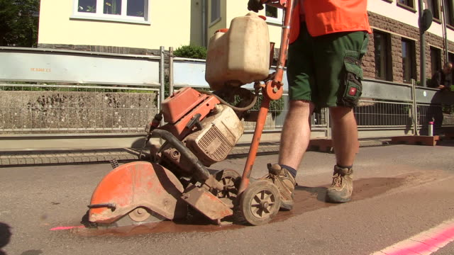 ms shot of workmen road cutter machine on street for works at sewage pipe / saarburg, rhineland palatinate, germany - ワーキングシニア点の映像素材/bロール