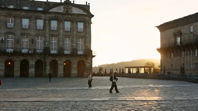 MS ZO PAN Shot of World Heritage Site of Santiago de Compostela in Galicia in Spain Obradoiro square at sunset, with tourists and pilgrims walking around