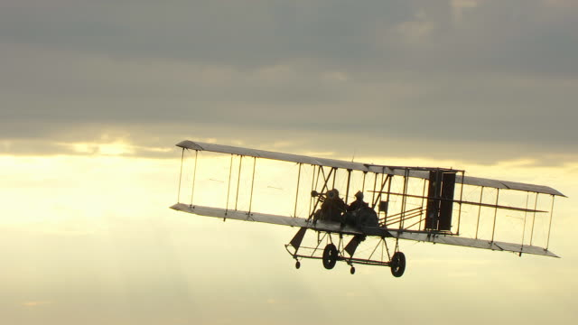 CU TS ZI AERIAL Shot of Wright B Flyer airplane flying in air with break in stormy sky / Dayton, Ohio, United States