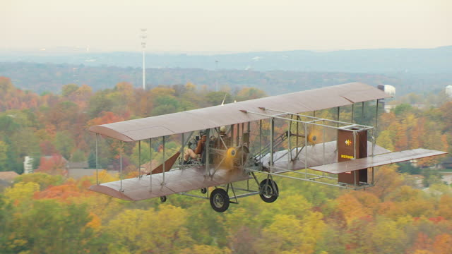 cu ts aerial shot of wright b flyer airplane flying over trees / dayton, ohio, united states - wright flyer stock-videos und b-roll-filmmaterial