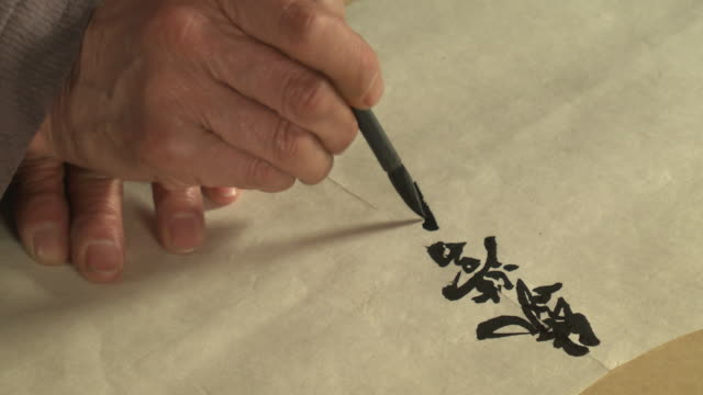 Shot of writing chinese script on kite with brush