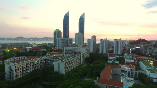 WS AERIAL shot of Xiamen downtown nearby sea at sunset/Xiamen,Fujian,China