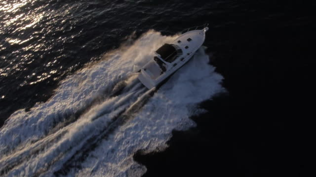 MS AERIAL TS HA SLO MO Shot of Yacht speed boat on ocean at sunset / Newport Beach, California, United States