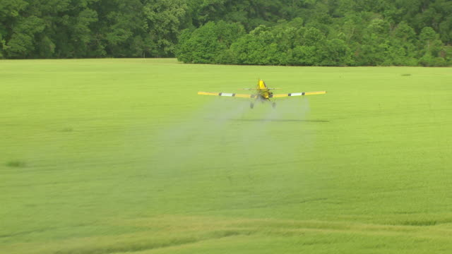 ms aerial ts shot of yellow crop duster swooping low over farm land releasing pesticides in madison county / mississippi, united states - insecticide stock videos & royalty-free footage