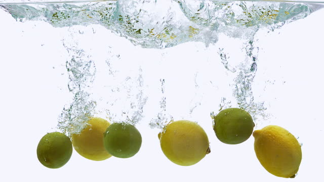 cu slo mo shot of yellow lemons, citrus limonum and green lemons, citrus aurantifolia, fruits falling into water and splashing against white background / calvados, normandy, france - lemon stock videos & royalty-free footage