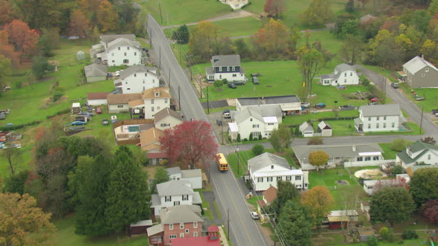 MS AERIAL ZI Shot of yellow school bus on local street in Schuylkill County / Brockton, Pennsylvania, United States