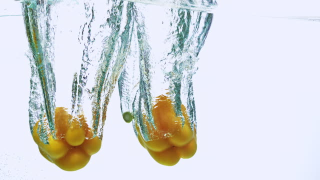 cu slo mo shot of yellow sweet pepper, capsicum annuum, vegetable falling into water against white background / calvados, normandy, france - calvados stock-videos und b-roll-filmmaterial