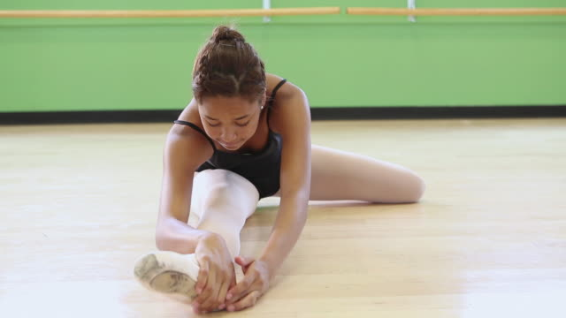 MS Shot of young ballet dancer stretching in studio / Santa Fe, New Mexico, United States