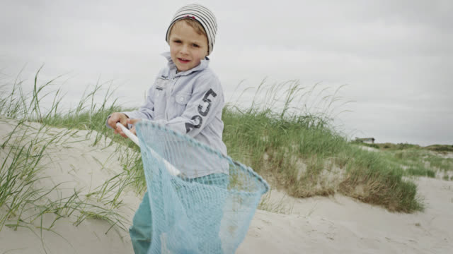 MS TD Shot of young boy at beach showing his small fishnet / St. Peter Ording, Schleswig Holstein, Germany