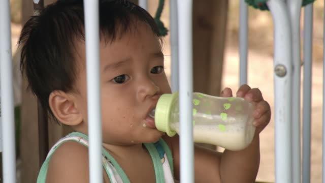 CU Shot of young boy drinking milk from bottle inside swinging crib / Chonburi, Thailand