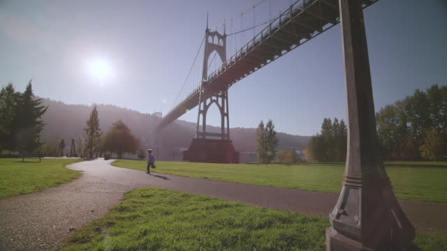 WS DS SLO MO Shot of young boy energetically running down sidewalk path in front of St. Johns Bridge along waterfront / Portland, Oregon, United States