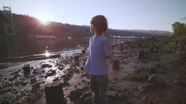 MS SLO MO Shot of young boy looking towards sunset as he standing on river beach shore with St. Johns Bridge and Willamette River fill frame / Portland, Oregon, United States