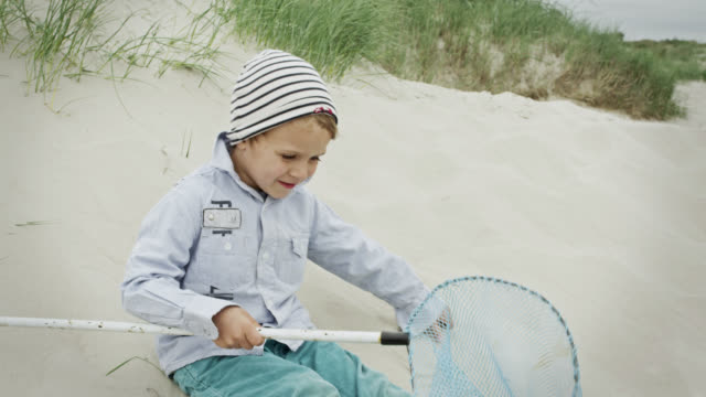 MS Shot of young boy lying on sand at beach, showing his small fishnet / St. Peter Ording, Schleswig Holstein, Germany