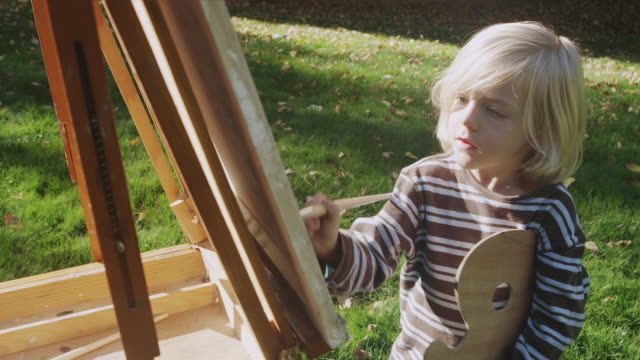 MS Shot of young boy paints on easel outdoors / Hillsboro, Oregon, United States