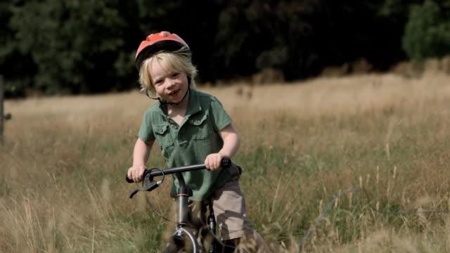 ms ts slo mo shot of young boy riding bike through field - jungen stock-videos und b-roll-filmmaterial