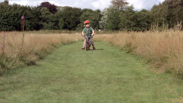 ms slo mo shot of young boy riding bike through wild flower field - スポーツヘルメット点の映像素材/bロール