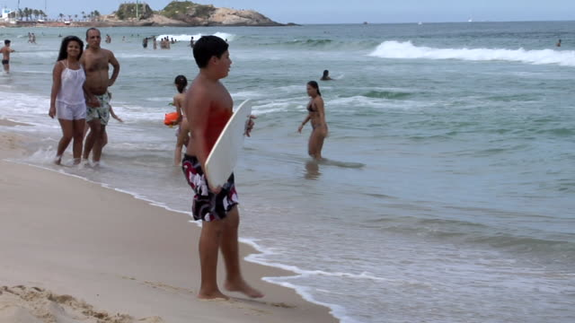 ms ts shot of young boy skim boarding at copacabana beach / rio de janeiro, brazil - skimboard stock videos and b-roll footage