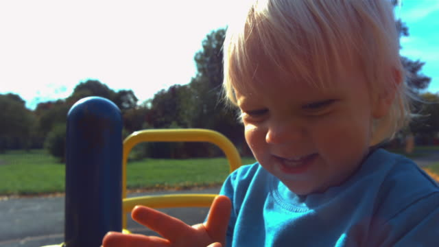 stockvideo's en b-roll-footage met cu slo mo shot of young boy spinning on roundabout in park - alleen jongens