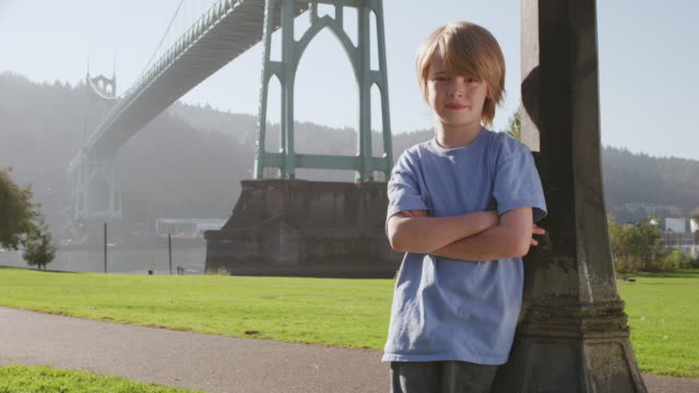 MS DS Shot of young boy standing confidently in front of St. Johns Bridge along waterfront / Portland, Oregon, United States
