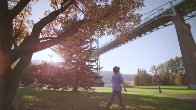 WS POV SLO MO Shot of young child running through beautiful sunny park with autumn fall leaves and colors with sun shines brilliantly and large steel St. Johns Bridge / Portland, Oregon, United States