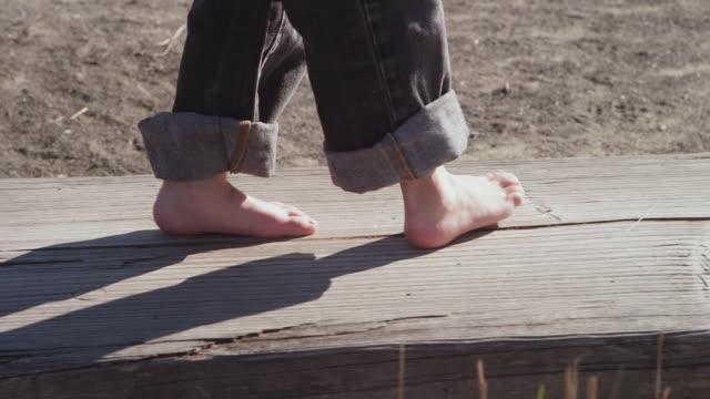 CU TS SLO MO Shot of young child's feet walking on bare wood playground bench / Beaverton, Oregon, United States
