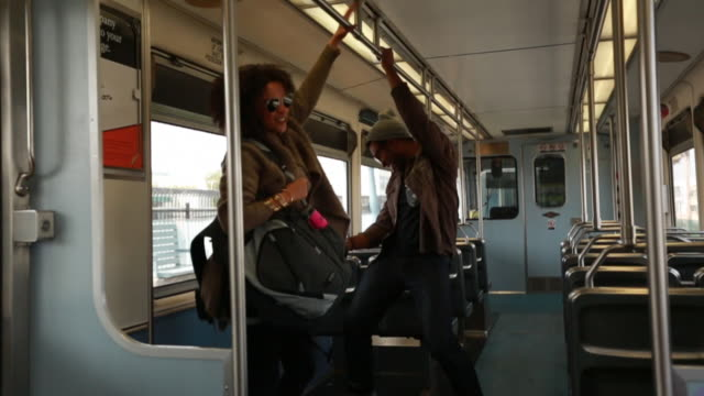 MS SLO MO Shot of Young couple dancing, laughing Inside metro train / Los Angeles, California, United States