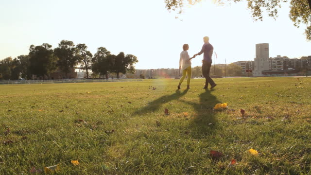 MS Shot of young couple embracing and kissing in park on sunny day having fun and smiling / Saint Paul, Minnesota, United States