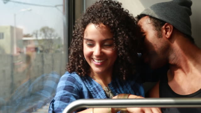 MS SLO MO Shot of young couple flirting, smiling and laughing on moving metro train Guy whispering in girls ear / Los Angeles, California, United States