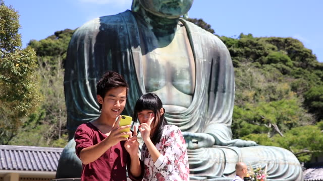ms shot of young couple taking commemorative photo with smartphone at great buddha / enoshima, kanagawa, japan - tourism点の映像素材/bロール