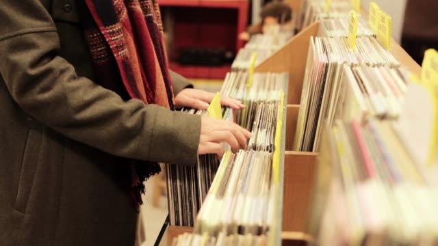 CU Shot of young female browsing and picking up vinyl record / Nakagusuku, Okinawa, Japan