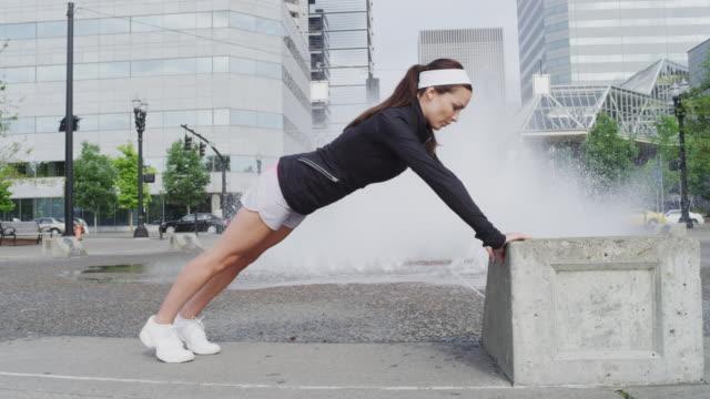 vídeos de stock e filmes b-roll de ms slo mo shot of young female jogger exercises by doing pushups on step at city fountain / portland, oregon, united states  - flexão de braço