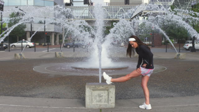 ms slo mo shot of young female jogger stretches at city fountain / portland, oregon, united states  - portland oregon bike stock videos & royalty-free footage