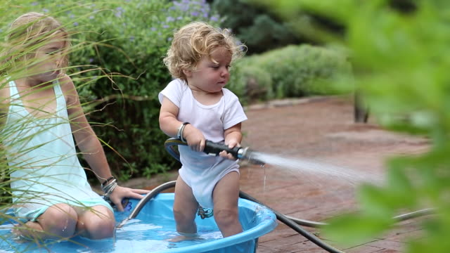 vídeos y material grabado en eventos de stock de ms shot of young girl and her baby brother playing in the baby pool / santa fe, new mexico, united states  - manguera