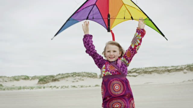 ms ts shot of young girl at beach, holding kite then letting it go and running towards it / st. peter ording, schleswig holstein, germany  - kid with kite stock videos & royalty-free footage
