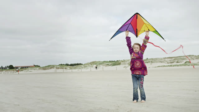 MS Shot of young girl at beach, holding kite then letting it go / St. Peter Ording, Schleswig Holstein, Germany