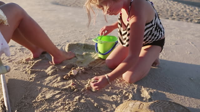 ms shot of young girl building sand castle at beach / st. simons island, georgia, united states - human limb stock videos & royalty-free footage