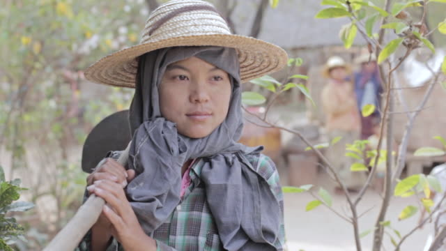cu shot of young girl carrying a headscarf and a straw hat / bagan, mandalay division, myanmar - straw hat stock videos & royalty-free footage