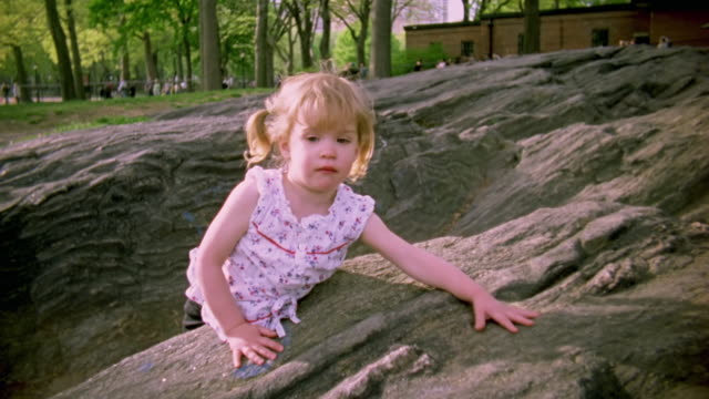 MS Shot of Young girl climbing down from rocks in Central Park / New York, United States