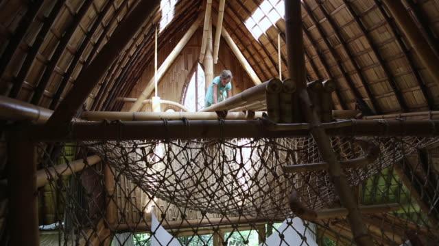 vídeos de stock e filmes b-roll de ms shot of young girl climbing in bamboo hut / ubud, bali, indonesia - bambu material