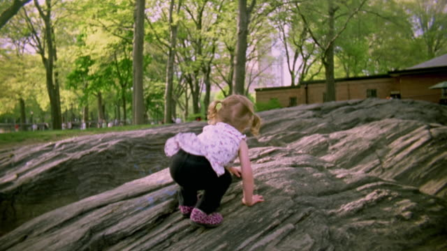MS Shot of Young girl climbing on rocks in Central Park / New York, United States
