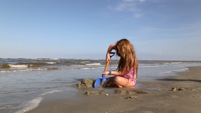 ms shot of young girl digging sand at beach / st simon's island, georgia, united states - bangle stock videos & royalty-free footage
