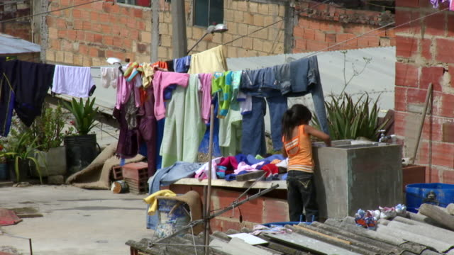 vidéos et rushes de ws shot of young girl does laundry next to a line where clothes hang to dry in ciudad bolivar slum / bogota, colombia - colombie