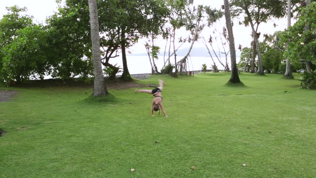 ws pan shot of young girl doing cartwheels in grass / ubud, bali, indonesia - ubud district stock videos & royalty-free footage