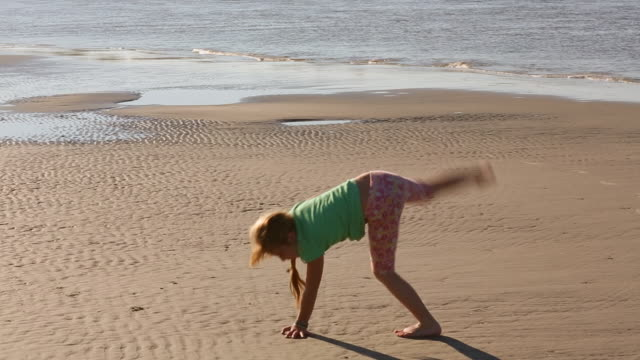 MS TS Shot of young girl doing cartwheels on beach / St Simon's Island, Georgia, United States